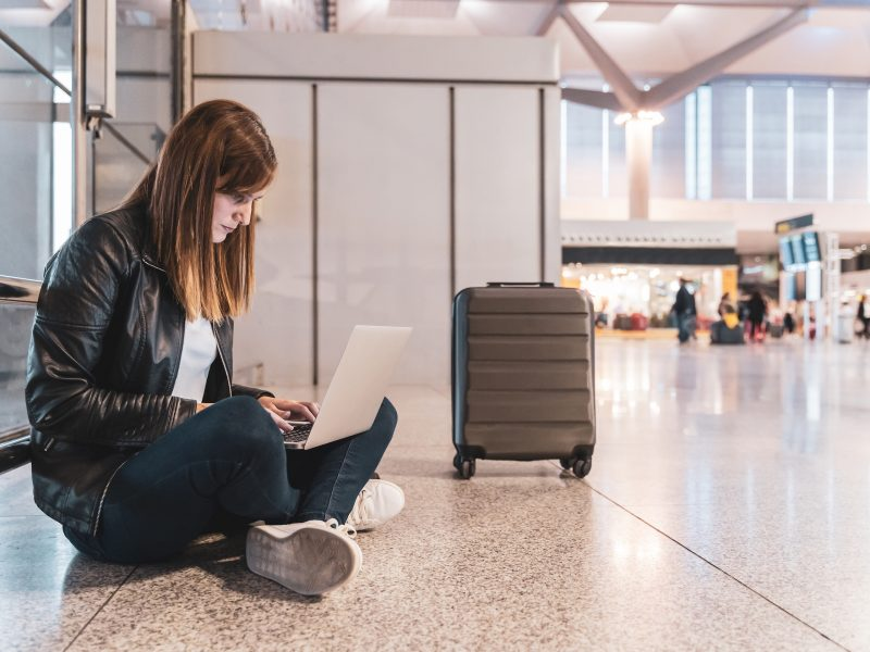Young Woman With Her Baggage And Her Laptop Waiting At The Airport Concept Of Travel And Vacation